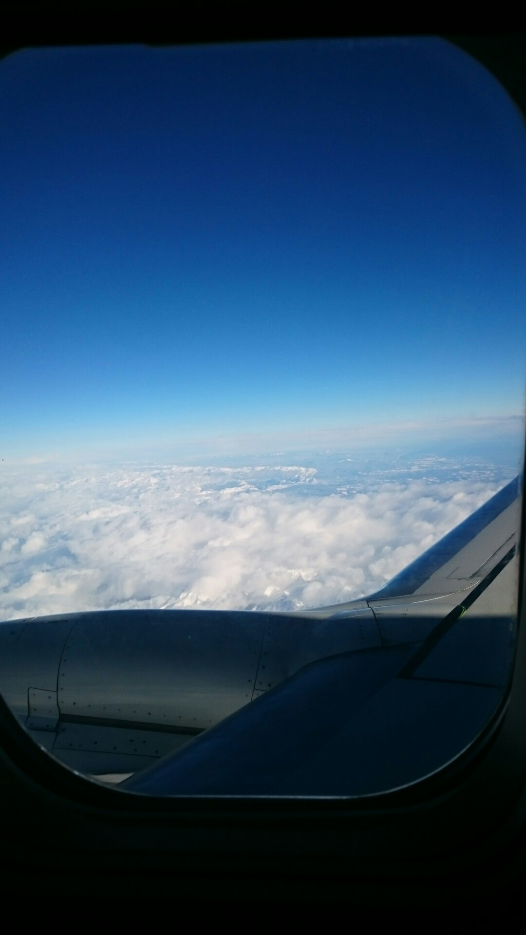 Picture taken out of airplane window of clouds from above.