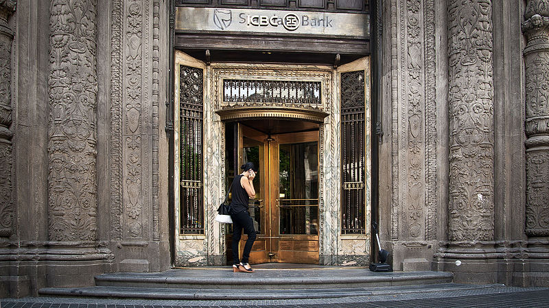 Person on phone walking into a wooden revolving door. Door is on an elaborately carved marble bank building.