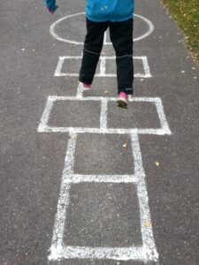 Image showing hopscotch painted on the ground, with child leaping from square to square. Child is wearing pink sneakers, balck pants and a blue jacket. We can see only the lower half of the child. There are leaves scattered around on the pavement.